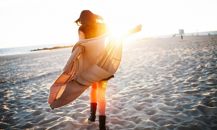 a-girl-walking-alone-on-sandy-beach-at-dawn-she-is-enjoying-sea-and-freedom-694x417